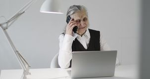 Cheerful old woman talking on a mobile phone at the office desk. Grandma works with a laptop indoors stock video