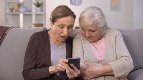 Cheerful old women watching photos on smartphone and laughing, good memories. Stock footage stock video