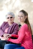 Cheerful old woman in wheelchair with her young granddaughter outdoor in hospital Royalty Free Stock Image