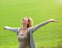 Cheerful older woman smiling with arms outstretched Stock Photography
