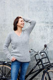 Cheerful older woman standing with bike Stock Image