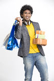 Cheerful overloaded Indian young man surprise with shopping bags and gift boxes Royalty Free Stock Images