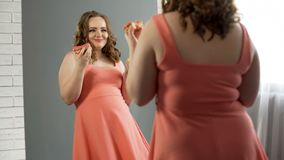 Cheerful overweight girl satisfied with her appearance eating donuts near mirror. Stock photo royalty free stock photos