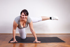 Cheerful overweight woman exercising Stock Image