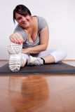 Cheerful overweight woman exercising/stretching Royalty Free Stock Images