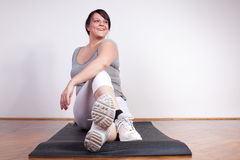Cheerful overweight woman exercising/stretching Stock Images