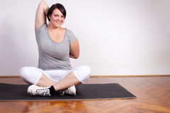 Cheerful overweight woman exercising/stretching Royalty Free Stock Photo