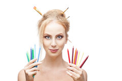 Cheerful painter girl. Young blond caucasian girl with brushes in hair holding color pencils when looking at camera and smirking royalty free stock photography