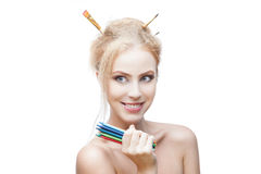 Cheerful painter girl. Young blond caucasian girl with brushes in hair holding color pencils while looking away and smiling stock image