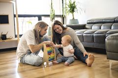 Cheerful parent playing with his baby girl on floor at living room. A Cheerful parent playing with his baby girl on floor at living room stock photography