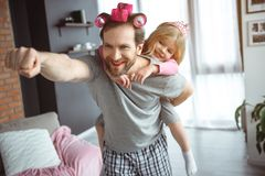 Cheerful parent playing in super hero with girl stock photos
