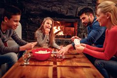 Cheerful parents and children playing cards at home stock photo