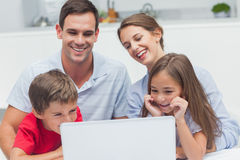 Cheerful parents and children using a laptop. In the kitchen stock photos