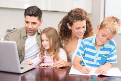 Cheerful parents colouring and using laptop with their children Royalty Free Stock Photo