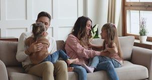 Cheerful parents and cute kids having fun tickling on sofa