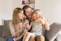Cheerful parents and daughter blowing bubbles in white modern ho royalty free stock photos