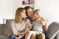 Cheerful parents and daughter blowing bubbles in white modern home Royalty Free Stock Photography