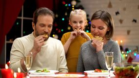 Cheerful parents and daughter eating cookies on Xmas eve, holiday together royalty free stock photography