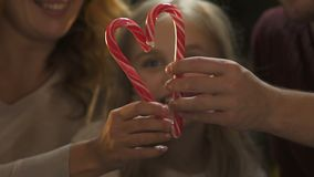 Cheerful parents forming heart from candy cane, sparkling Christmas decorations