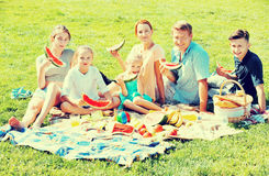 Cheerful parents with four kids enjoying watermelon on picnic. Positive parents with four happy kids enjoying watermelon on picnic on sunny summer day Stock Photo