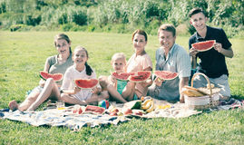 Cheerful parents with four kids enjoying watermelon on picnic. On sunny summer day Stock Photo