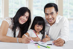 Cheerful parents help their child studying Royalty Free Stock Photography
