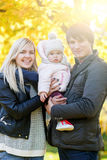 Cheerful parents holding daughter on hands in autumn park royalty free stock image