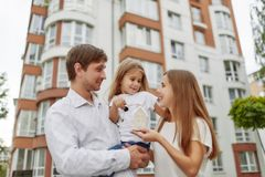 Happy family in front of new apartment building. Cheerful parents holding their little daughter and keys to their new home in apartment building on the back Stock Image