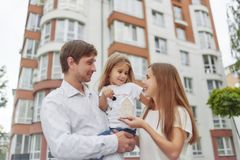 Happy family in front of new apartment building. Cheerful parents holding their little daughter and keys to their new home in apartment building on the back Stock Photo