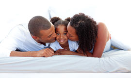 Cheerful parents kissing their daughter Royalty Free Stock Photos