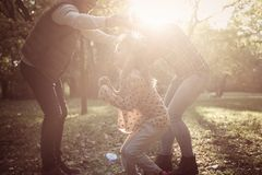 Cheerful parents with one child playing in nature together. stock image