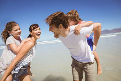 Cheerful parents piggybacking their children at beach stock photography