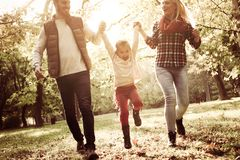 Parents and smiling girl playing together in park. stock photos