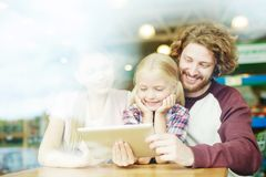Funny video. Cheerful parents and their daughter watching curious and funny video in tablet at leisure stock images