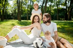 Cheerful parents and their son and little daughter, dressed in white clothes, take rest on the picnic in the park. Happy stock photos