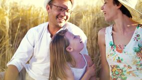 Cheerful family in summer outfits sitting in wheat field