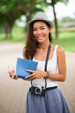 Cheerful pastime. Vertical portrait of a cheerful girl with a camera and a book enjoying her summer pastime Stock Photography