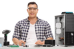 Cheerful PC technician repairing a computer. Cheerful PC technician sitting at a table and repairing a computer on white background Royalty Free Stock Photography