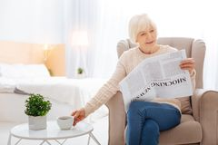 Cheerful pensioner drinking tasty tea while sitting with a newspaper and smiling. Reading newspaper. Cute calm aged woman looking happy while sitting with an Stock Photo