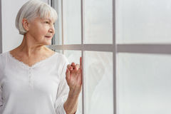Cheerful pensioner watching at closed window in hospital Stock Image