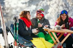 Cheerful people having fun after skiing in resort with snow equi. Cheerful people having fun after skiing in mountains resort with snow equipment Stock Photography