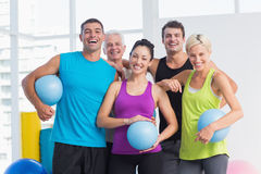 Cheerful people with medicine balls in fitness studio. Portrait of cheerful people with medicine balls in fitness studio Stock Photo