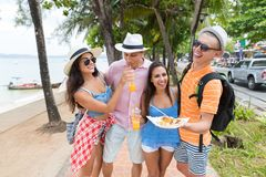Cheerful People On Seaside Group Of Friends Holding Asian Street Food Walk In Park Near Sea Young Tourists Man And Woman. Together On Vacation royalty free stock photography