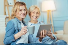 Smiling woman holding a cup while her granny sitting with a tablet. Cheerful people. Cheerful smiling young women holding a cup of tea while her positive kind Stock Images