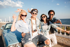Cheerful people standing and showing peace sign near vintage car Stock Image