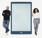 Cheerful people standing beside a tablet Royalty Free Stock Image