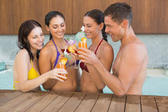 Cheerful people toasting drinks in the swimming pool Royalty Free Stock Image