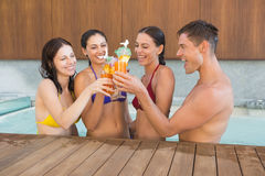 Cheerful people toasting drinks in the swimming pool Stock Photo