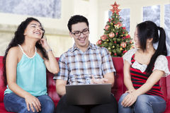 Cheerful people using laptop with christmas tree Stock Photos