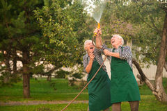 Cheerful people and water hose. Couple of seniors in garden Royalty Free Stock Photo
